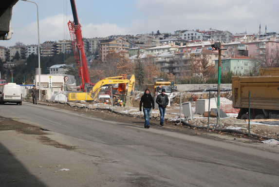 Öğrenciler, inşaat alanının yanında akan trafiğin ortasında.